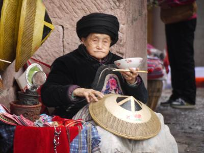 Minority woman in Fenghuang selling hats