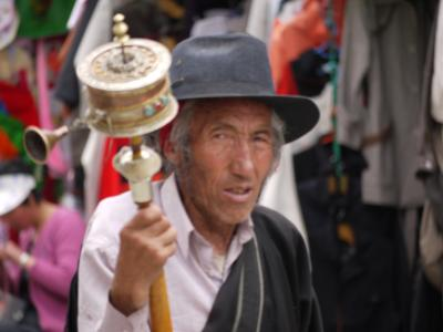 Old man spinning prayer wheel in Barkhor, Lhasa