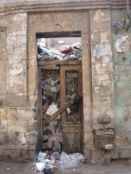 Entrance of a ruined house in Old Cairo, now completely 	 filled with garbage