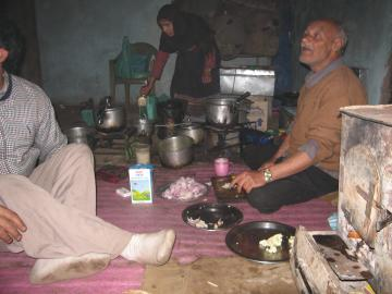 Old man cooking dinner in the village